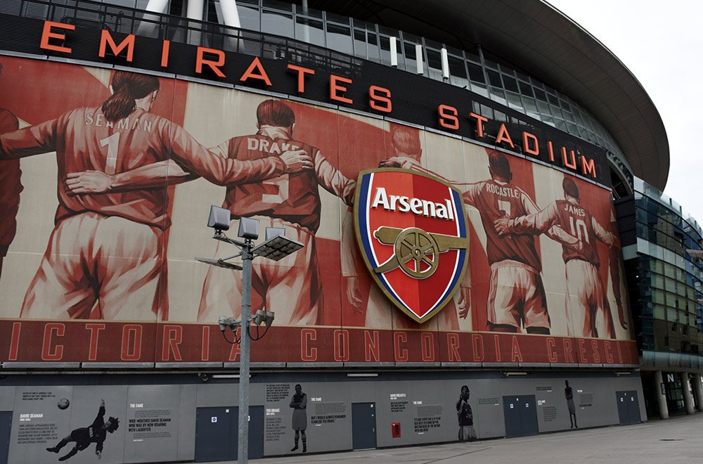 Outside of Emirates Stadium with images of Arsenal football players on the wall