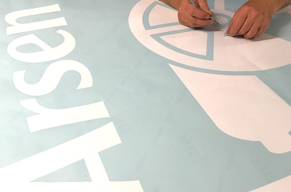 a persons hands cutting out vinyls for Arsenal fooball club