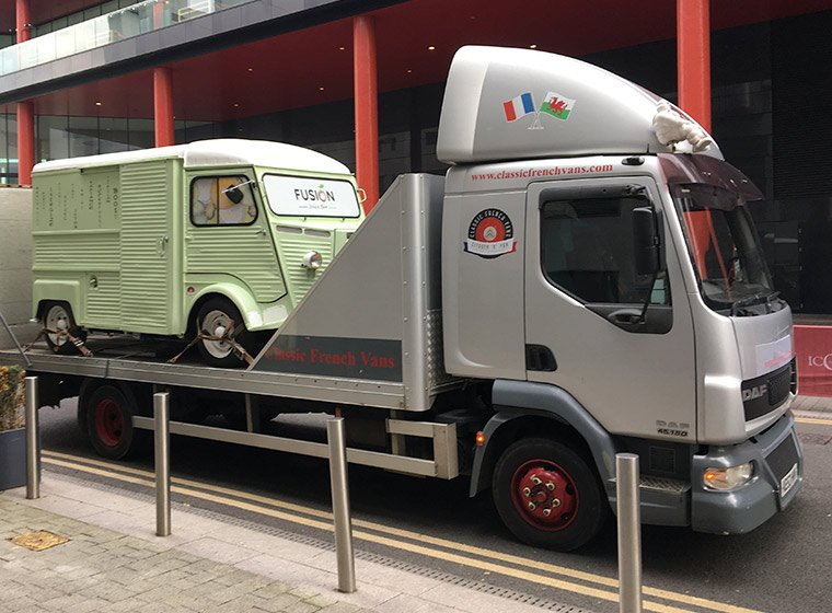 A light gree Citroen HY van conversion on the back of a transport lorry